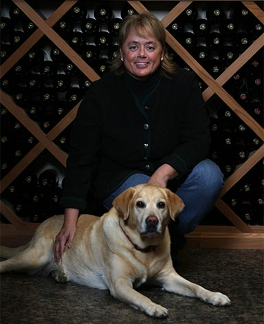 Debra Mathy with her dog in front of wines